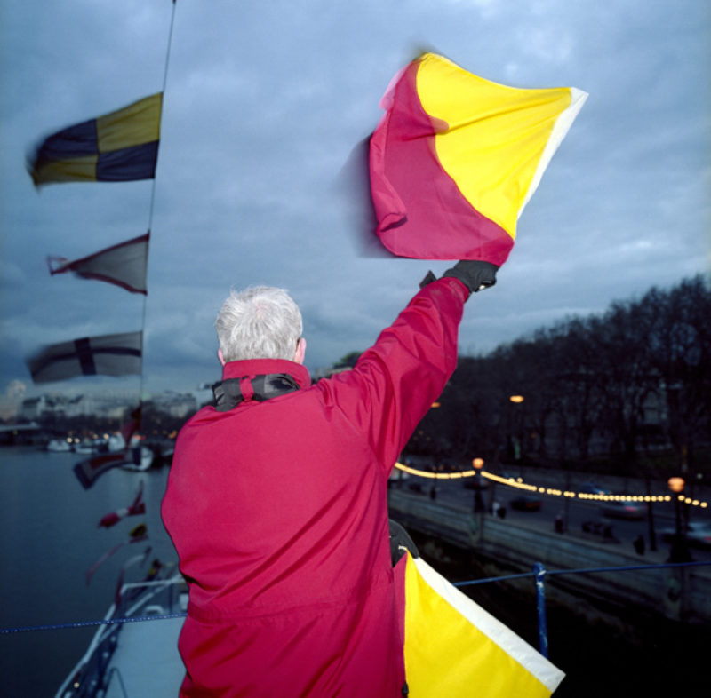 Semaphore signaller aboard HMS President for 'Message', an event created by Beth Derbyshire and commissioned by the National Maritime Museum for Remembrance Sunday 2005