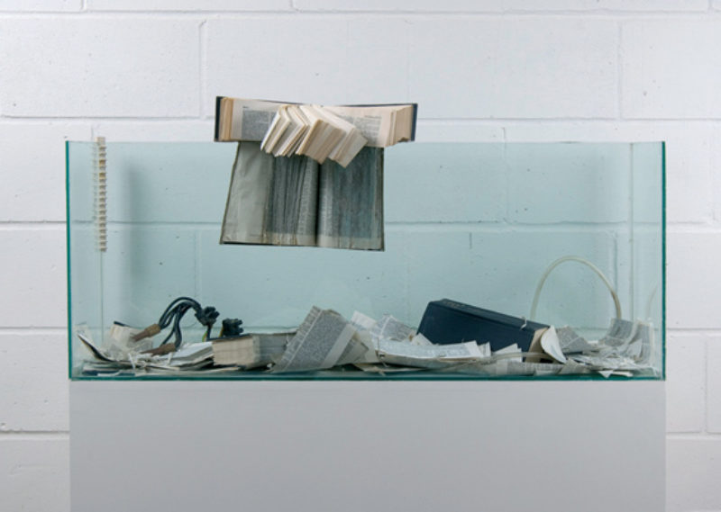 John Latham 'Distress of a Dictionary', 1988, glass fish tank containing torn books, electrodes and cables