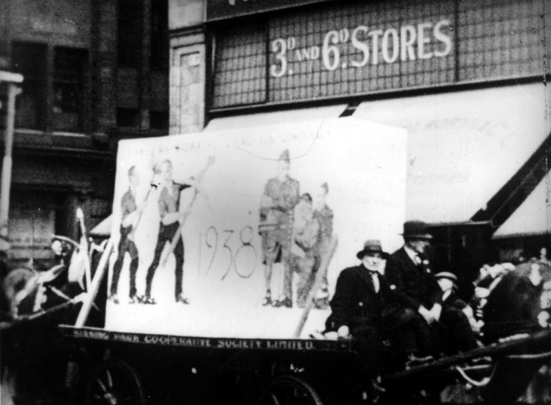 Film still, Challenge to Fascism Glasgow's May Day (1938) by Helen Biggar. Kinning Park Co-Operative Society float, in front of the Woolworth's Store. Still courtesy of Billie Love Historical Collection.